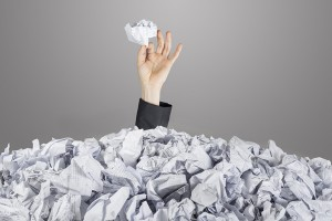 Person under pile of documents
